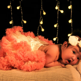 Baby Girl Under Twinkle Light At Home